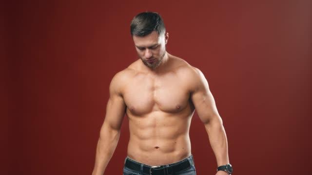 vidéos et rushes de jeune type athlétique retenant un pot de nutrition de sports et une tasse. - body building