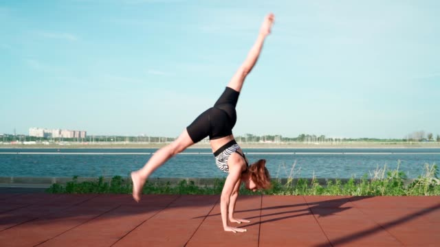 Young Athletic Gymnast Woman is training on Lake Background. Beautiful Girl Is Exercising Outdoors. Stretching Exercises and Flexibility. Sport and Healthy lifestyle concept Young Athletic Gymnast Woman is training on Lake Background. Beautiful Girl Is Exercising Outdoors. Stretching Exercises and Flexibility. Sport and Healthy lifestyle concept doing the splits stock videos & royalty-free footage