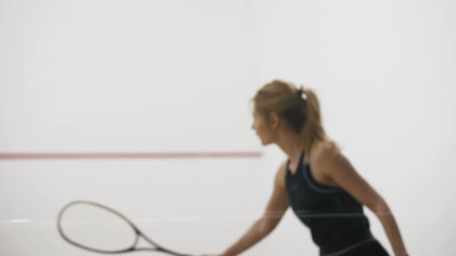 Young athletic man and woman play squash together in the squash court, slow motion, close up shot