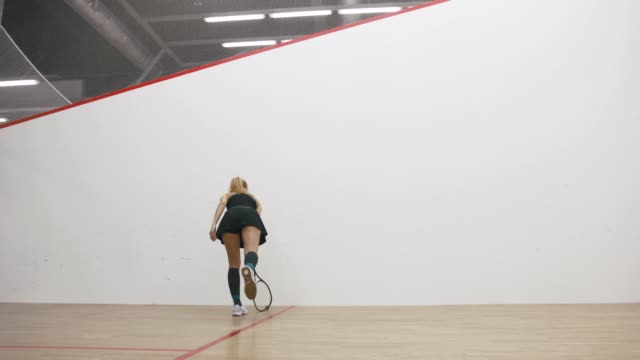 Young athletic man and woman play squash together in the squash court, slow motion, low angle view