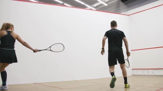 young athletic man and woman play squash together in the squash court, slow motion, low angle view - zucchini video stock e b–roll
