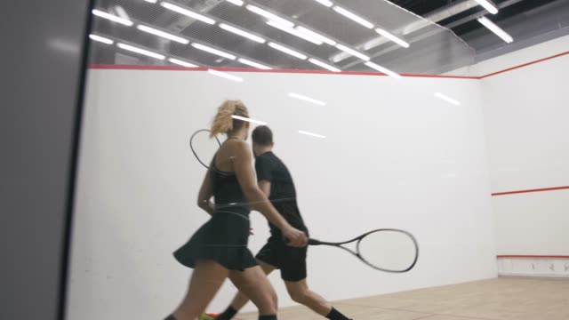 Young athletic man and woman play squash together in the squash court, slow motion, camera is behind the glass
