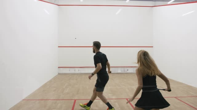 Young athletic man and woman play squash together in the squash court, slow motion