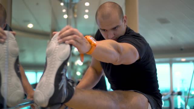 vídeos de stock, filmes e b-roll de o homem atlético novo faz estiramentos exercitam na ginástica - perna termo anatômico