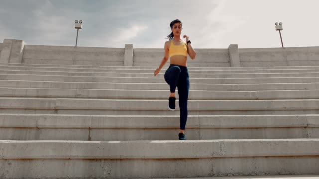 Young athletic woman doing sports training on urban stadium stairs Young sporty woman with smartwatch exercising and running down urban stadium stairs during sports workout cross training stock videos & royalty-free footage