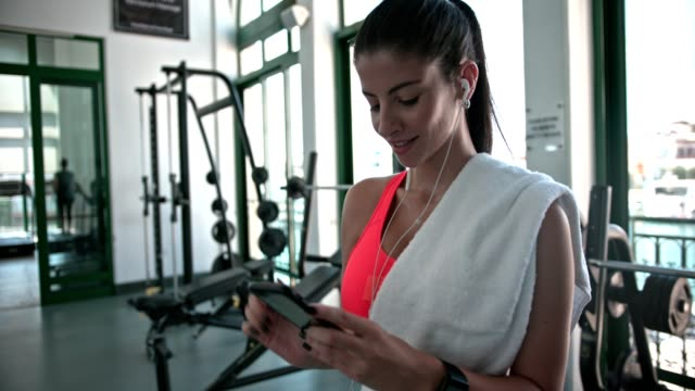 Young athletic woman listening to music on smartphone at gym Young fit woman listening to music using smartphone and texting on gym workout break health club stock videos & royalty-free footage