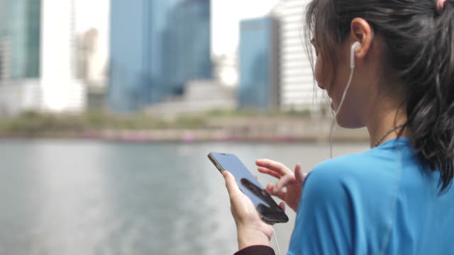 Young athletic woman listening to music on smartphone in City