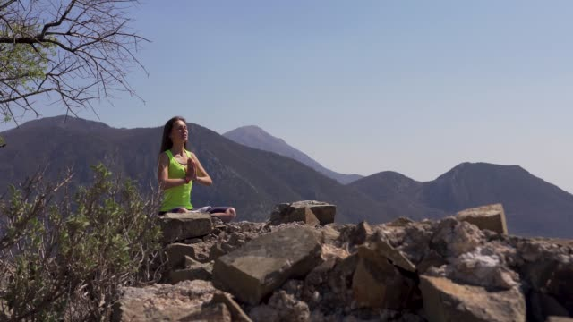 Young athletic woman meditating on the top of a mountain