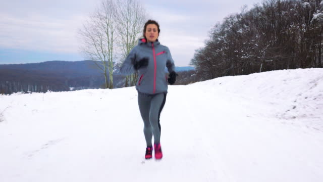 Young athletic woman running on a snow during cold winter day. video