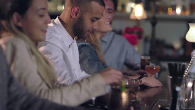 vídeos de stock, filmes e b-roll de jovem atraente americano africano olhando para seu celular, enquanto está sentado entre as pessoas em um bar - costumer