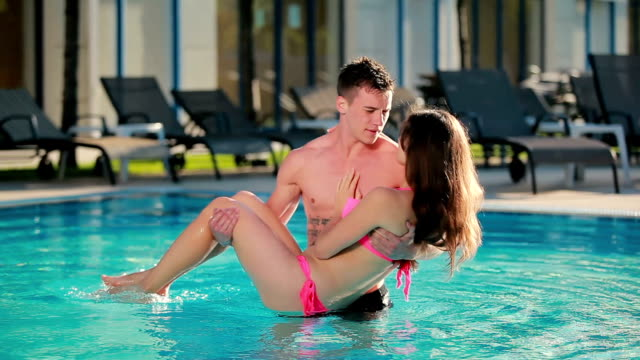 Young atrractive guy circling his beautiful girl in the pool