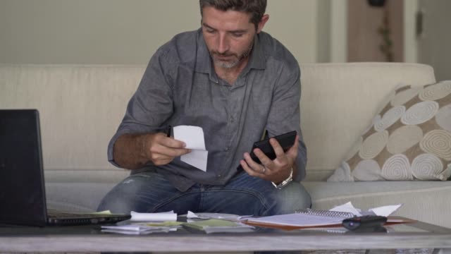 young attractive and busy man at living room sofa couch accounting monthly expenses and debt payments using calculator counting domestic finance income and tax paperwork at modern apartment