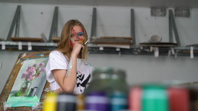 a young attractive artist with a brush in her hands and with a face in the paint looks into the camera - cavalletto attrezzatura per arti e mestieri video stock e b–roll