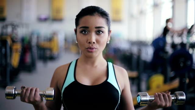 若い魅力的なアジアの女の子を、ダンベル、エクササイズ - 人の筋肉点の映像素材/bロール
