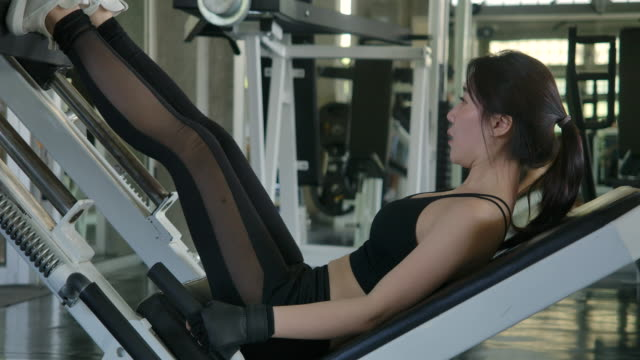 young attractive asian woman training legs in gym. athletic woman training her quads at machine press at gym. slow motion. healthcare, fitness and bodybuilding. - kulturystyka filmów i materiałów b-roll