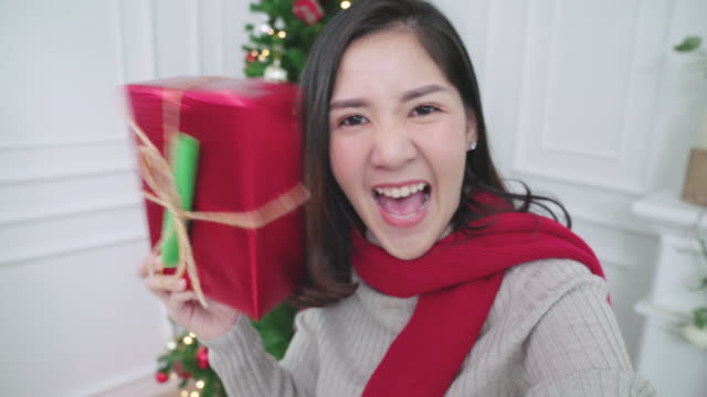 Young attractive asian woman using smartphone making video chatting with her friend in living room feeling happy with christmas tree background.