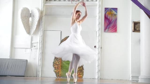 vídeos de stock e filmes b-roll de young attractive ballerina in white tutu performs pirouette in spacious studio - tule têxtil