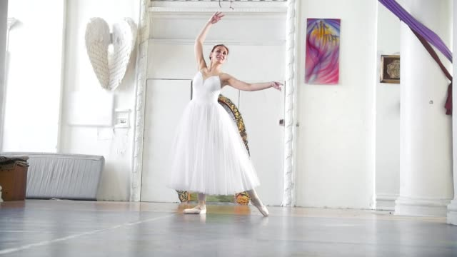 vídeos de stock e filmes b-roll de young attractive ballerina in white tutu posing in spacious white studio - tule têxtil