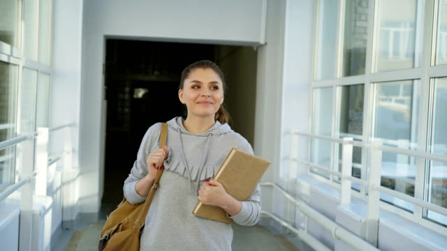 giovane bella ragazza attraente sta scendendo lungo un ampio corridoio universitario spazioso guardando su e via sognante passando per i suoi amici agitando le mani a loro e andando avanti - passare davanti video stock e b–roll
