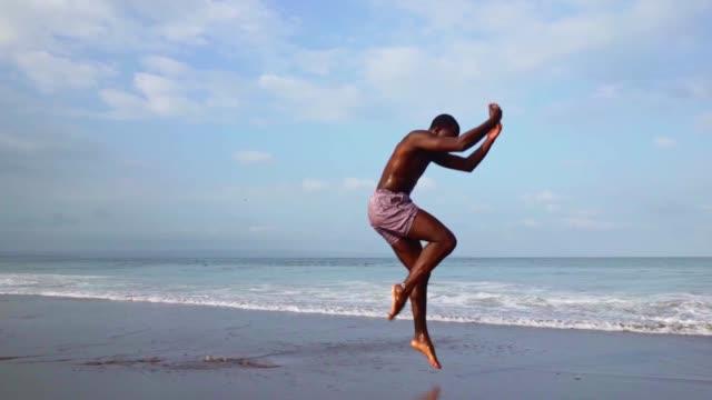 vídeos de stock, filmes e b-roll de jovem atraente bailarino negro se apresentando na praia - balé