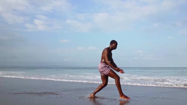 Young attractive black ballet man dancer performing at the beach Contemporary ballet dancer performing at the beach .combined gimbal shot on young attractive and athletic black African American man dancing by the sea ballet dancer stock videos & royalty-free footage