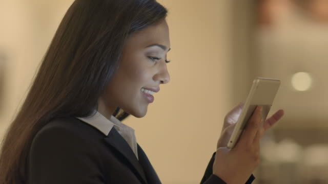 young attractive black women using tablet computer searching the web online. african american female in business suit connecting with social media. urban lifestyle background - служащая стоковые видео и кадры b-roll