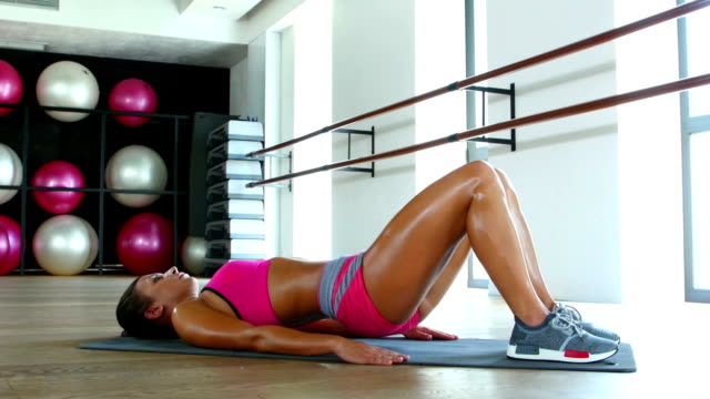 Young attractive blonde woman exercising on a mat. Dolly shot video