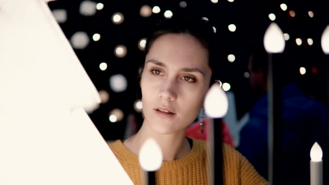 Young attractive brunette girl at the store chooses lamps, Christmas decor video