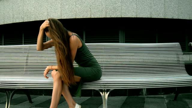ドレスの路上で座っている若い魅力的なブルネット - チャームポイント点の映像素材/bロール