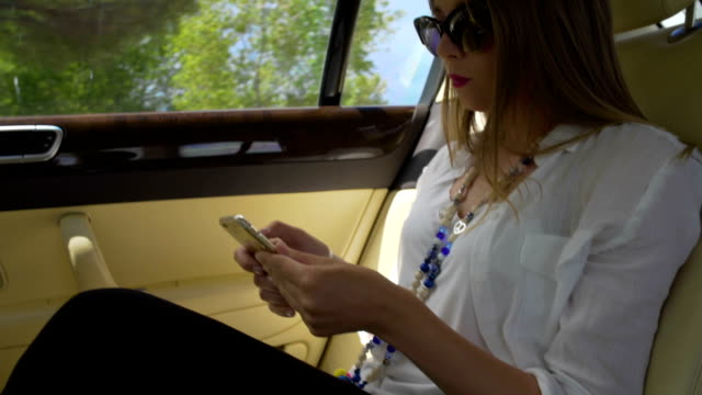 Young attractive businesswoman riding in taxi and surfing the net on smartphone video