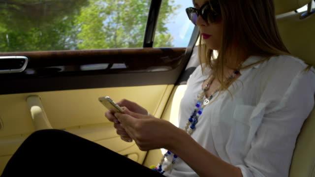 junge attraktive geschäftsfrau im taxi fahren und surfen im netz auf smartphone - teurer lebensstil stock-videos und b-roll-filmmaterial