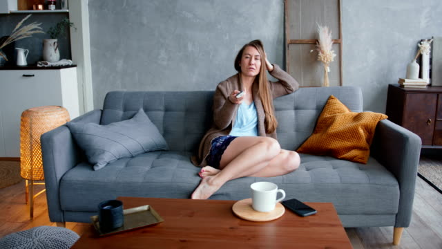 young attractive caucasian blonde woman procrastinates, bored from switching tv channels alone at home on self isolation - divano procrastinazione video stock e b–roll