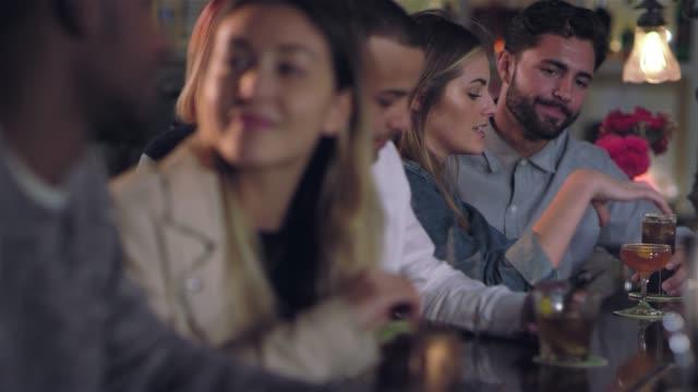 vídeos de stock, filmes e b-roll de jovem casal caucasiano atraente falando em segundo plano em um bar - costumer