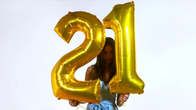 med young attractive caucasian female holding air balloons shaped as number 21, birthday celebration concept. 60 fps slow motion shot - 20 24 anni video stock e b–roll