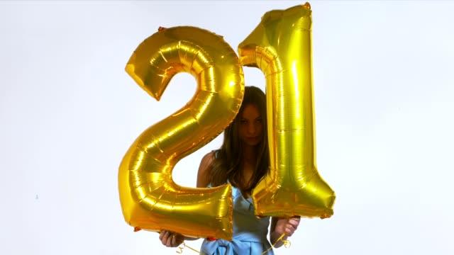 vídeos de stock, filmes e b-roll de med jovem atraente caucasiana segurando balões de ar em forma de número 21, o conceito de celebração de aniversário. câmera lenta de 60 fps tiro - 20 24 anos