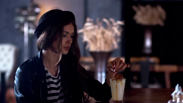 CINEMAGRAPH - Young attractive Caucasian girl with a milk shake in modern cafe video