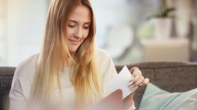 vídeos de stock e filmes b-roll de young attractive caucasian woman receiving letter and smiling for joy - correio