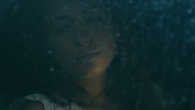 Young attractive Caucasian woman sitting in the car during rain, drops fall on the window. video