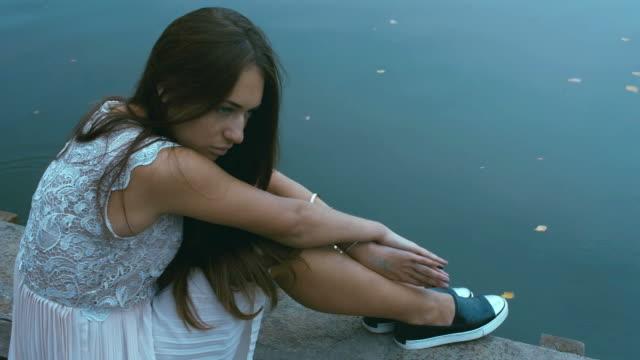 vídeos de stock, filmes e b-roll de jovem mulher caucasiana atraente sentada em um antigo cais. - largo descrição geral