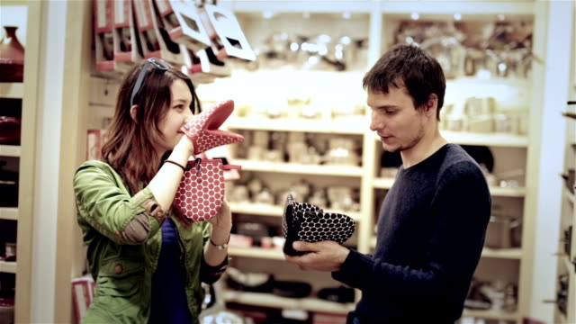Young attractive couple have fun in shopping mall. Woman wear kitchen potholder on hand video