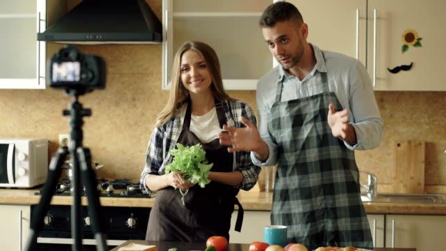 vídeos de stock, filmes e b-roll de jovem casal atraente em avental atirando comida vídeo blog sobre culinária na dslr câmera na cozinha - blogar