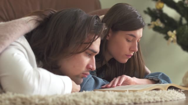 Young attractive couple in love lying on the carpet in the bedroom covered with a blanket reading a book and cheerfully discusses