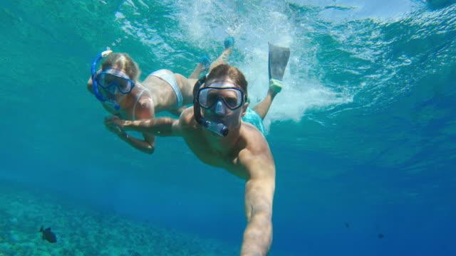 vídeos y material grabado en eventos de stock de pov de joven pareja atractiva snorkeling juntos - tubo