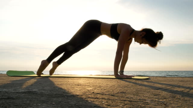 Young attractive female doing yoga exercises near the water video