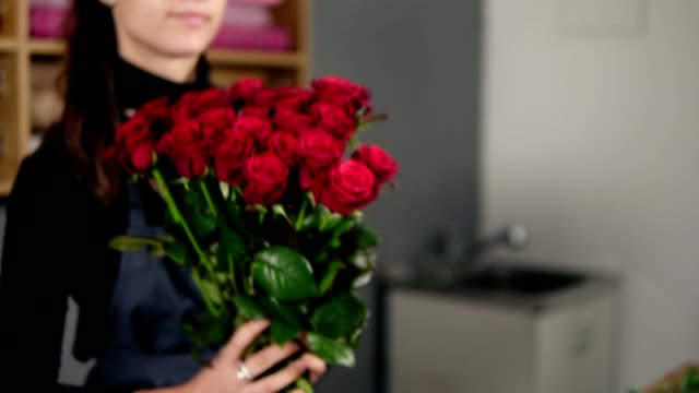 Young attractive female florist arranging bouquet of beautiful red roses at flower shop. Slowmotion shot
