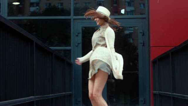 MED Young attractive female in vintage dress jumping in the street. video