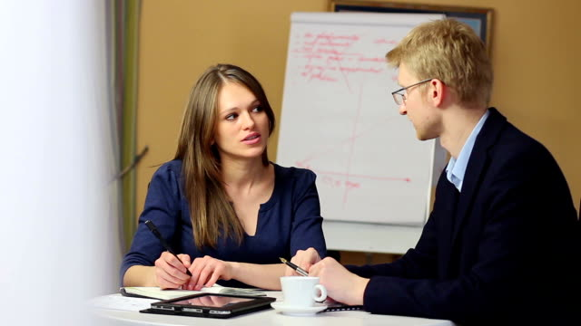 Young attractive female office worker with man on work meeting video
