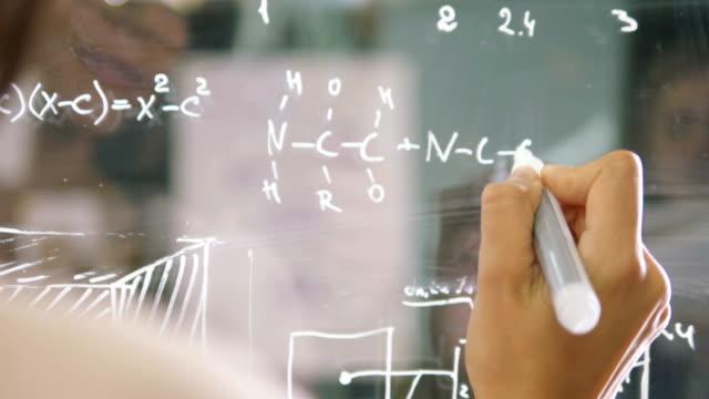 young attractive female office worker writing on glass whiteboard, close up - symbol matematyczny filmów i materiałów b-roll