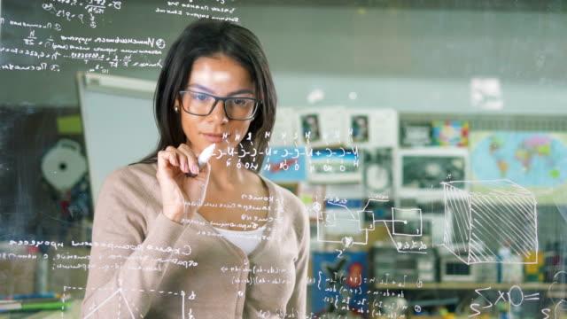young attractive female office worker writing on glass whiteboard - symbol matematyczny filmów i materiałów b-roll