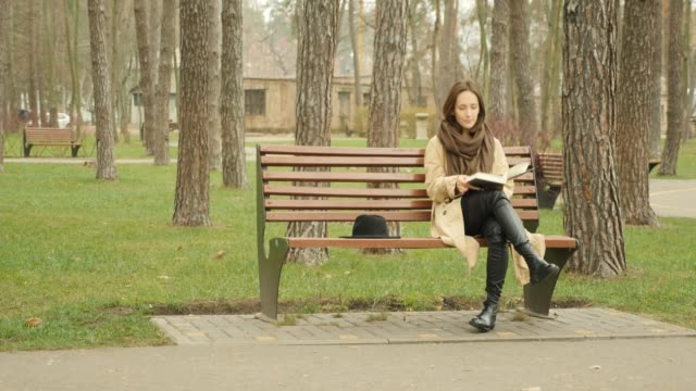 young attractive female sitting on a bench in park alone reading a book wearing brown trench and scarf. studying concept. - садовая скамья стоковые видео и кадры b-roll